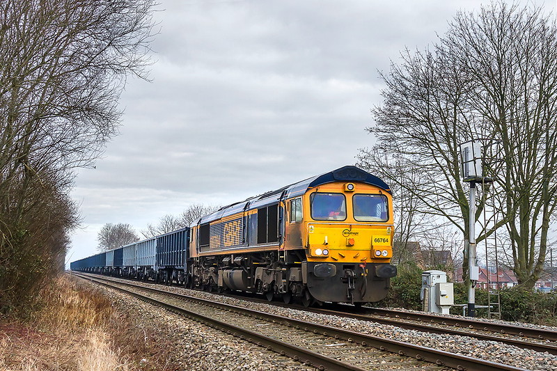 23rd |Jan 2017:  6V42 is a GBRf service from Wellingborough to Whatley Quarry to refill the boxes with stone.  It is booked to go through the station at Westbury but usually  uses the New Line 'AKA Cut Off- Avoider'.  Powered bu 66764 it is pictured from the public foot crossing thar used to give access to the engine shed