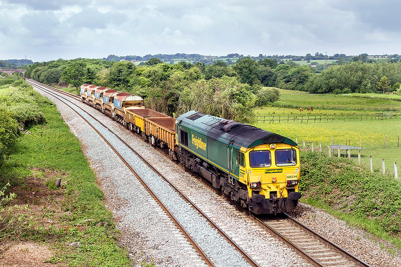 9th Jun 2017:  66514 trundles East through Fairwood with 7C28 from Fairwater Yard to Westbury.  The two JNAs contained odd lengths of rail for the recycling plant.