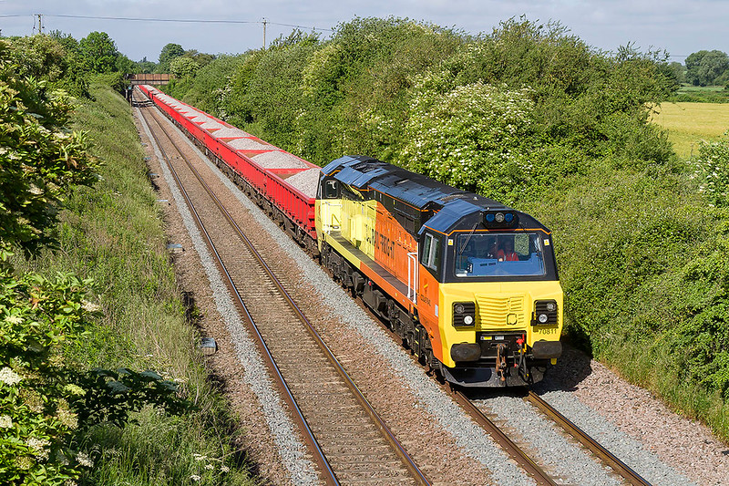 10th Jun2017:  Dashing through Edington is 70811 at the head of 6C27 from Westbury to Bourton, to the east od Swindon.  The load of 31  MXA Lobsters making a nice contrast to  the rest of the scene