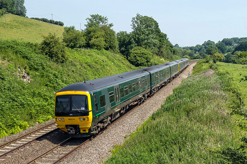 21st Jun 2017:  With the Glastonbury Festival about to start 1Z33 the 10.36 from Padding to Castle Cary special carrying revelers runs through Cole.  166214 leading 165102 are pictured  from the old S & D embankment where the two lines used to cross.