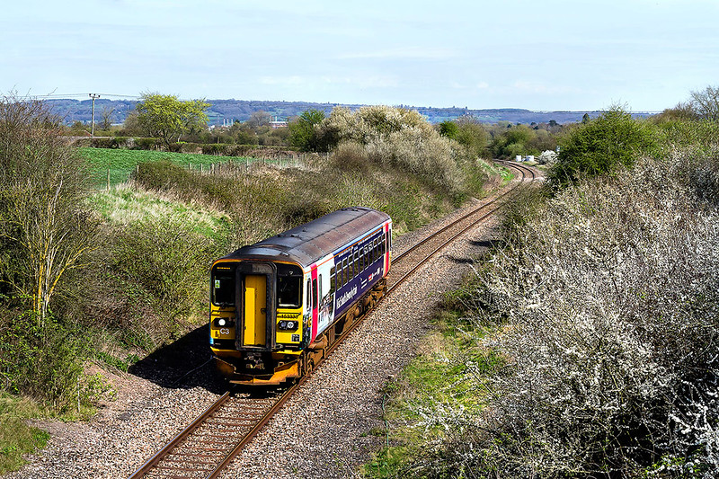 30th Mar 2017:  Spring is here at last. The 12.47 from Swindon to Frome passing ter site of Broughton Gifford Halt that closed in the 1950s.  153333 is branded to advertise  visiting South Devon.  This line was singled in 1968.