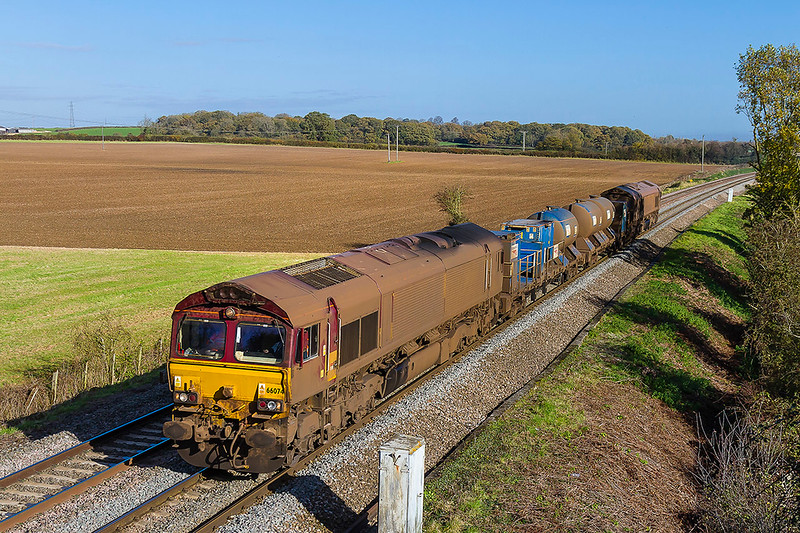 6th Nov 2017:  Getting dirtier by the day are 66074 & 66027 as they work 3J13 the RHTT squirter back to St Blazey from Westbury.  The cleaered location is Berkley Marsh near Clink Road Junction