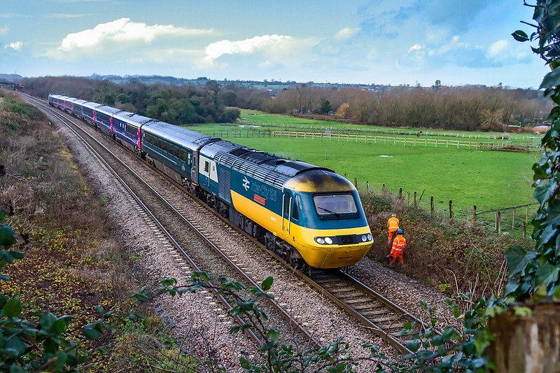 7th Dec 2018: Pioneer HST power car 43002 approaches Westbury as it heads 1A79 the 06.45 from Penzance to Paddington.  How many more chances will I have to photograph this one before it is withdrawn?  The two high viz are weilding chain saws  and cutting back and thingnearing the track.