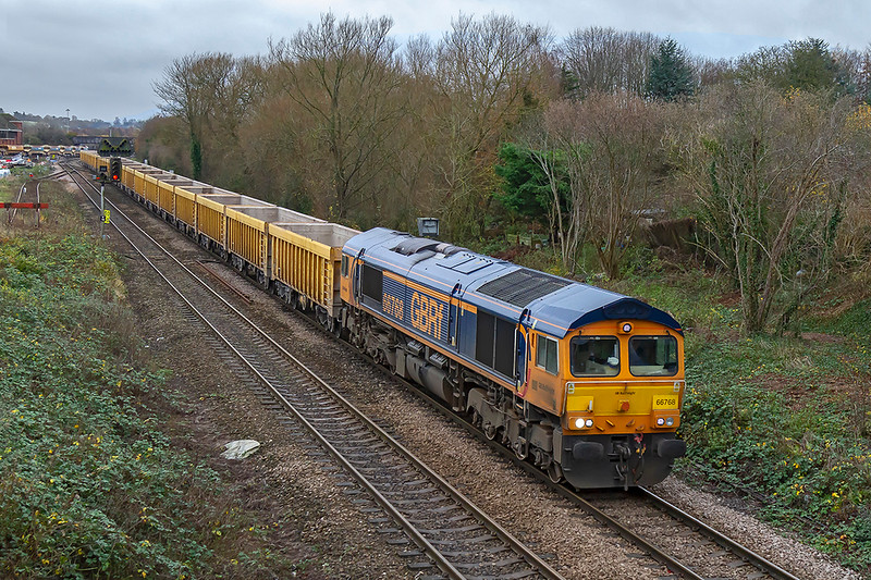 6th Dec 2018:  Making a change from the commonly used 59003 sees 66768 leaving Westbury in charge of 6M50 from Westbury to Stud Farm for a ballast refill.
