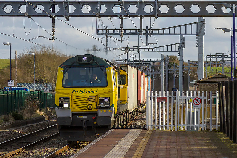 12th Feb 2018:  Captured as it runs through Chilsey is 70008 headint 4M61 FROM Southampton to Tafford Park.  This overhead gantry suppor emits enormous amaounts of noise every time an electric trai passes onany of the four lines at this point.  The same noise can just be heard from a similar gantry further to the west.