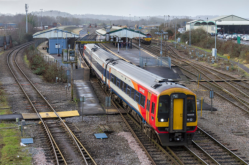 4th Jan 2018:  159008 left Waterloo at 09.20 at part of 1L21 to Exeter St Davids.  At Salisbury it split to become 1V22 to Bristol Temple Meads and is seen here as it departs from Westbury.  I shall rue the day when this attractive, IMHO, livery is confined to memory. 66093 can be seen in the Up Loop waiting for the 'off' with the Whatley to St Pancras stone