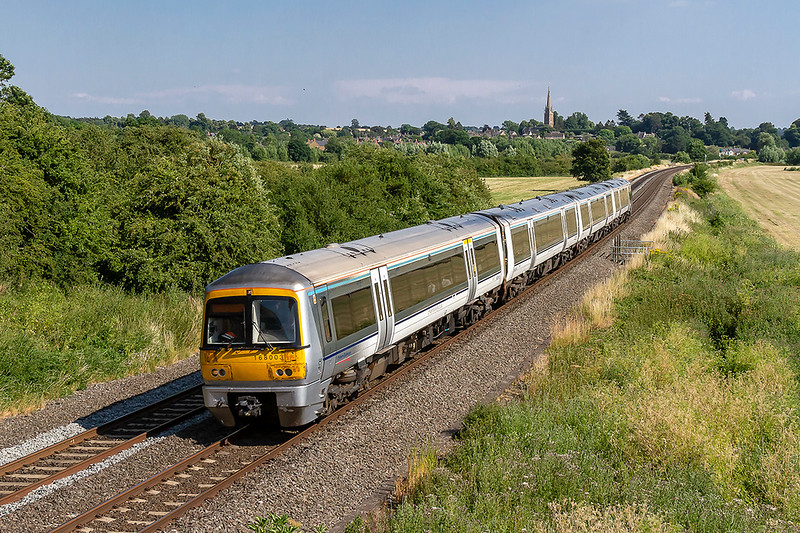 5th Jul 2018: Kings sutton's Church of St Peter & St Paul  stands in the distace as Chiltern Railways 168003 nears the end of it's journey at Banbury. 2M63 had started  from Marylebone at  4 pm