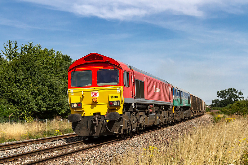 25th Jul 2018:  Running 85 minutes late is 7C29.  Powered by 59204 with 59005 tucked inside the Acton to Merehead empties are pictured as they pass the White Horse Bussiness Park between Trowbidge and Westbury.  Thank you driver for the wave.