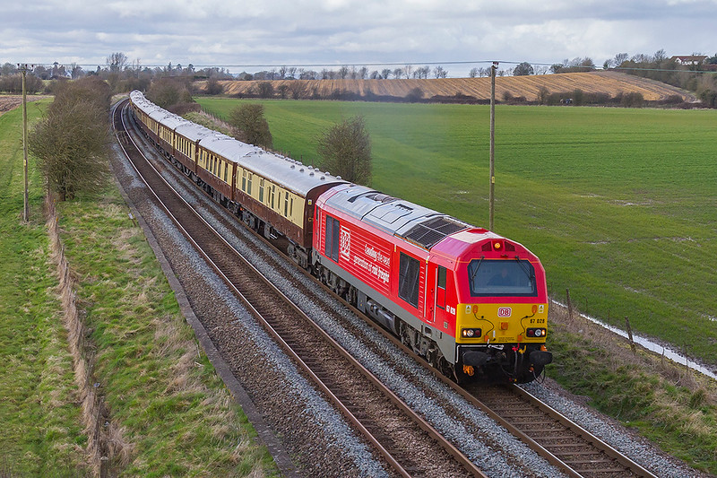 "27th Mar 2018:   Taken from a bridge on the Warminster By-Pass is 67028 0n the point of 1Z30 the Belmond Pullman returning to Victoria from Bath Spa.  67024 in Pullman livery  is on the other end. The  writing on the side reads ""leading the next generation of rail freight"""