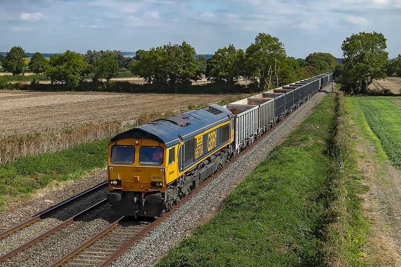 5th Sep 2018:  6V42 is four and a half hours into it's journey and there is not far to go. 66704 'Colchester Power Signalbox' is working the 07.55 from Wellingborough to Whatley through the fields at Baynton Farm in Edington