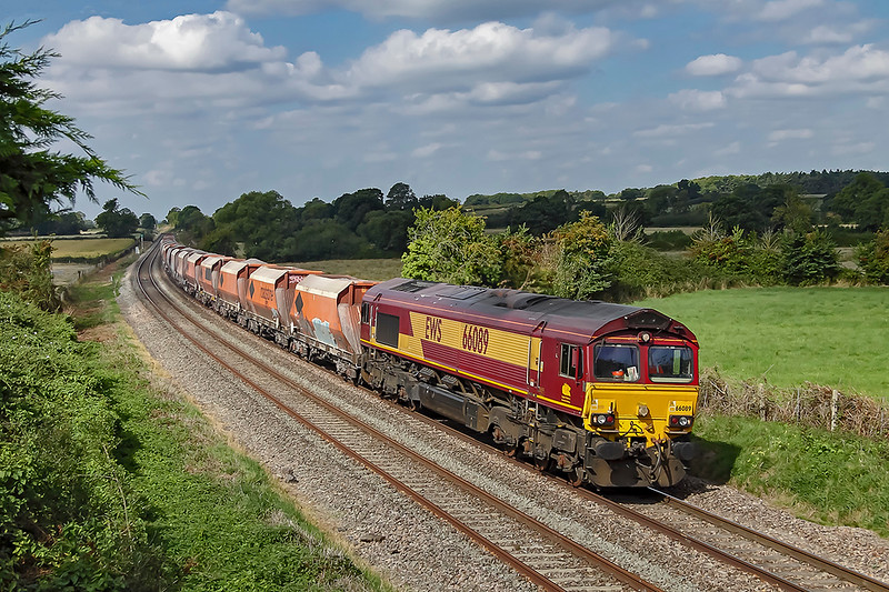 5th Sep 2018:  66089 has just started the almost continuous 17 mile grade  to Savernake.  There a 1 mile down hill stretch between Woodborough and Pewsey.  6M20 with the old RMC hoppers is working from Whatley Quarry to Hayes & Harlington