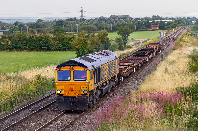 4th Aug 2019: Nearing Westbury as it runs through Heywood is 6G70 in the hands of 66719 'Metro Land'.  The short but motley collection od wagons are  being brought back to base from Filton Abbey Wood.