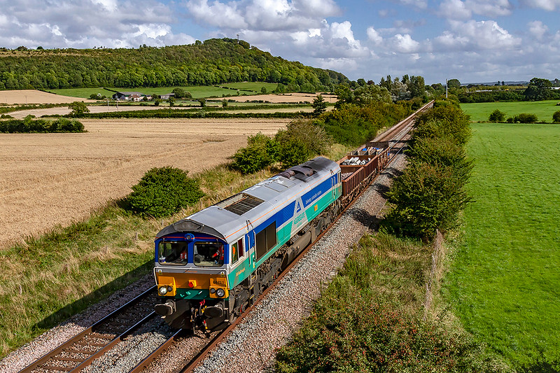 19th Aug 2019:  With Arn Hill in the background 6V41 the afternoon return departmental from Eastleigh to Westbury is pictured as it runs  between Warminster and Westbury.  Although wearing Aggregate Industries livery like the 590s it is actually GBRf 66711 that is now named 'Sence'.