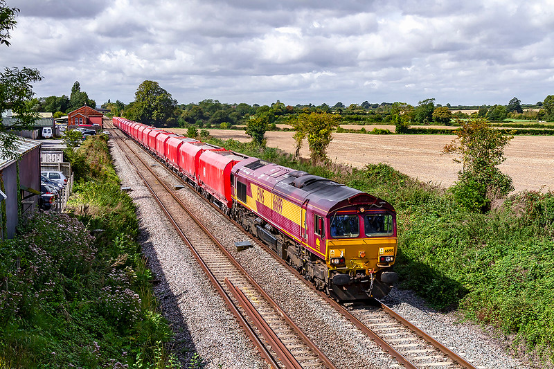 29th Aug 2019:  With the Schenker red hoppers showing up well  6M20 from Whatley to St Pancras Churchyard Siding. is passing through the site of Edington & Bratton station.  Providing the power is 66199 one of the declining number that are still in their original EWS livery