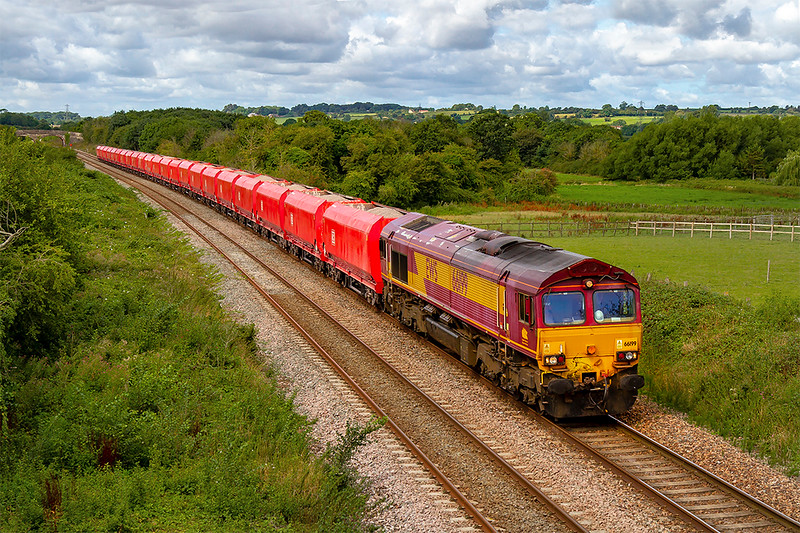 15th Aug 2019:  66199 is on the point of 6M20 from Whatley Quarry to St Pancras Siiding.  The Schenker red hoppers were originally used for coal traffic but have been cut down for use on stone workings.  They will probably be scrapped when Freightliner take over this traffic later this year.  The location is Fairwood.