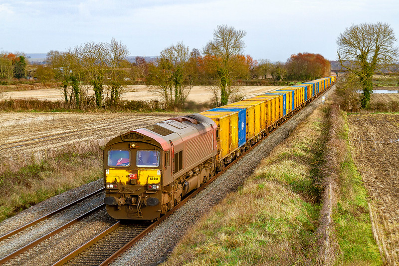 16th Dec 2019:  With this day being the start of the new time tables freight that used the Top Road from Wootton Bassett to Bristol Parkway are being diverted to run via the Berks & Hants line.  A very dirty 66018 is tasked with taking the  'Pong Liner' ' 6C03, from Northolt Sidings to Severnside SITA,  The location is Cowleaze Lane in Edington.