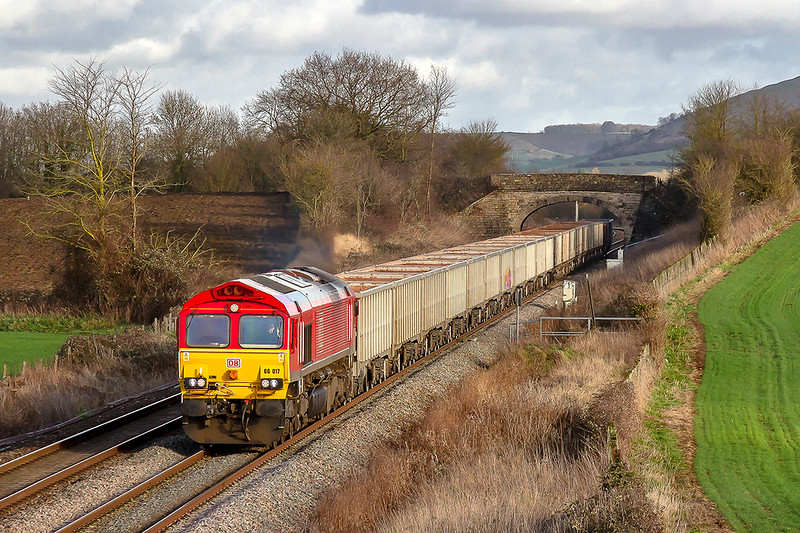 7th Feb 2019:  Just catching some sun as it crosses the foot crossing at Fairwood  is 66017.  6C58 is bringing the empty boxes back from Oxford Banbury Road to Whatley Quuarry. The light had faded by the yime it had reached the bridge on which I am standing.