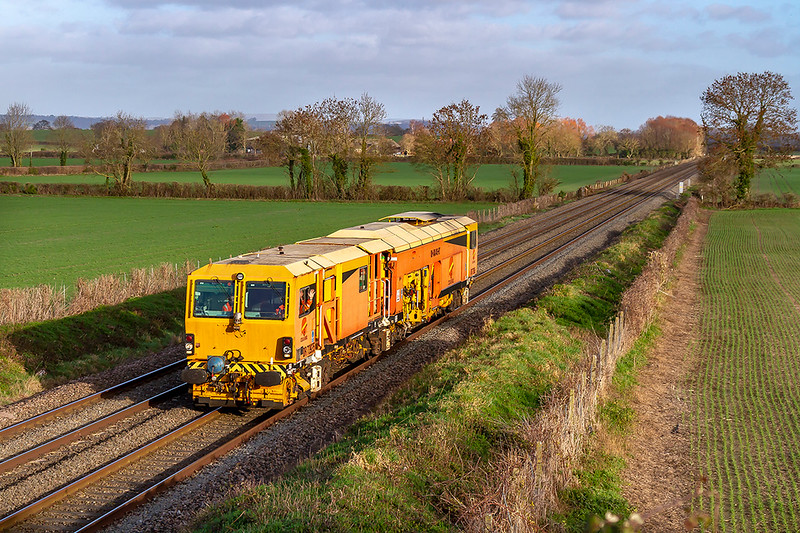 8th Jan 2019: Passing through Baynton Farm in Edington is Colas Tamper DR73935.  6J42 running from  Southall Isu (S & Te) to Westbury had started on time at 11.28 but was now running 26 minutes early.  Obviously the driver was happy as he is giving a very friendly wave.