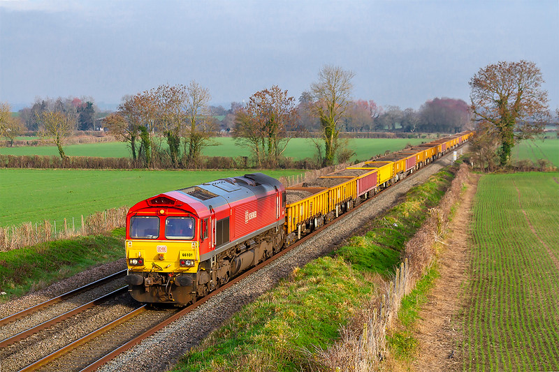 20th Jan 2019:  66101 is in charge of a long rake of mainly JNAs loaded with spent ballast. 6W03  started from Southall and is making for Westbury which is only a few miles from this bridge on Cowleaze Lane in Edington