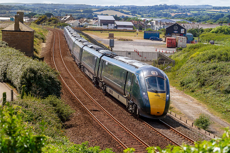 12t Jul 2019:  Leaving Penzance at 16.00 1A97 and 4 minutes tater it is captured as it passes through the site of Marazion Station with the old station building on the left. 802108 is doing the job today,