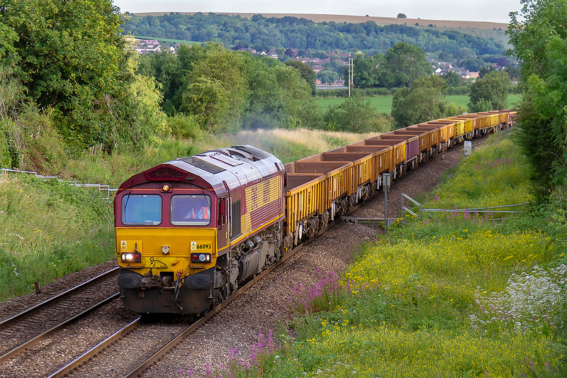 21st Jul 2019: Heading to Gloucester Over Junction from Westbury is 66093 and a rake of empty JNA & MLAs. The picture is taken from Church Road in Heywood looking back towards Hawkeridge Junction.