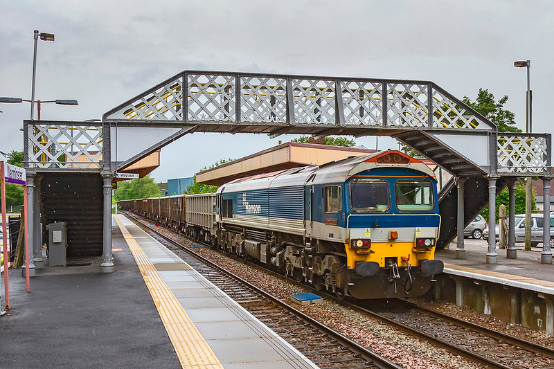 10th Jun 2019:  ith a motley bunch of boxes on tow 59101 'Village of Whatley' runs through Warminster Station, 7V16 is running from Fareham to Whatley Quarry.  I wonder if, when Freightliner take over the Mendip workings, these 591s will be repainted, If it happens this will say goodbye to the oldest livery currently in use.  The forecast afternoon rain was just starting and shows against the underside of the foot bridge stairs.