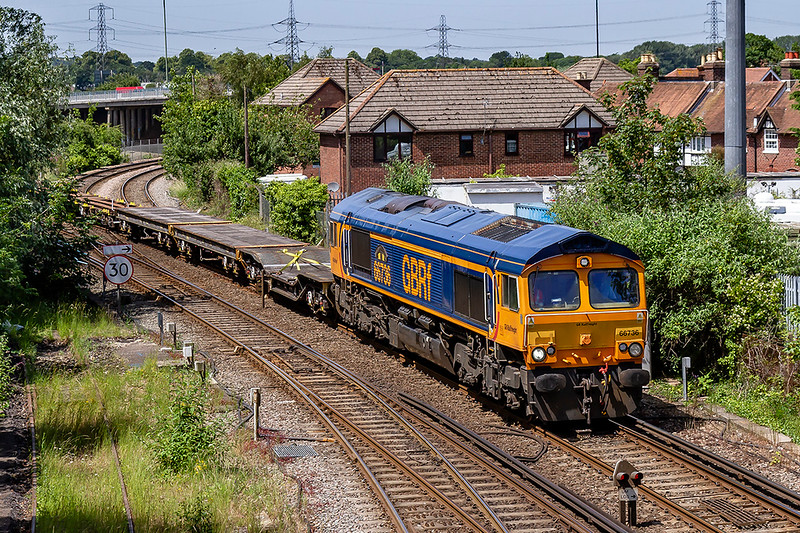27th Jun 2019:  Crossing the junction with the line from Romsey at Redbridge is 66736 'Wolverhampton Wanderers.workingfrom Marchwood MOD to Bicester MOD. Empty flats of course.