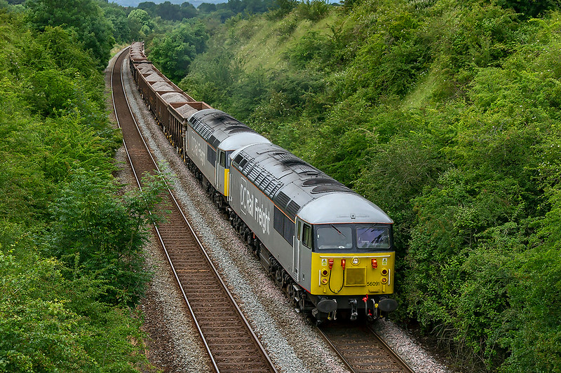 25th Jun 2019:  On the second day of the new service, carrying crushed spent ballast, to Southampton Up Yard from Westbury is pictured on the steep grade through Upton Scudamore.  Now with the pair of DCR 56s reversed 6Z91 has 56091 on the. point which will also lead on the return emptes in the morning.