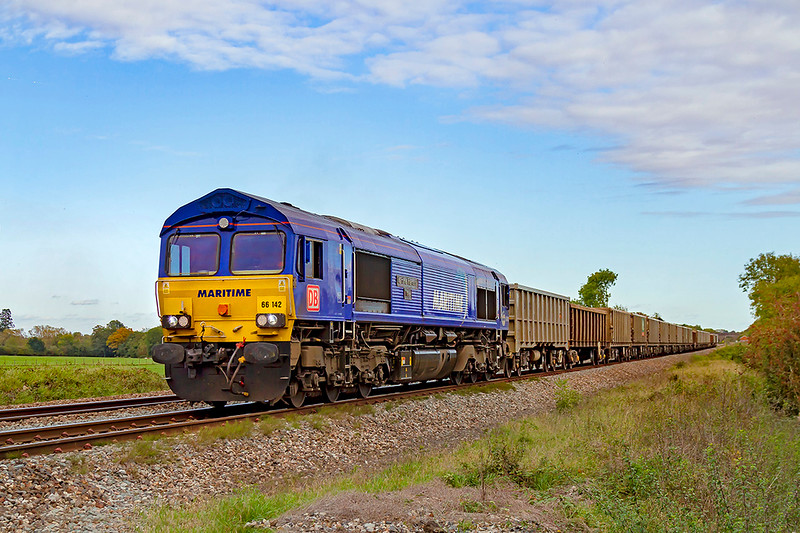 22nd Oct 2019:  This is the first time that a DBC maritime blue class 66 has worked a stone service from the Somerset quarries.  66142 'Maritime Intermodal Three' is captured at Masters Crossing near Fairwwood as it works 6C58 from Oxford Banbury Road to Whatley Quarry.  Difficult lighting though.