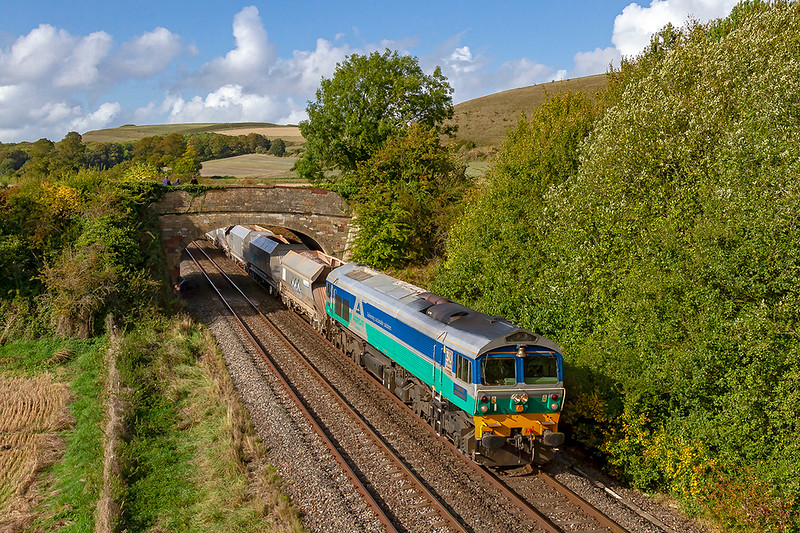 24th Sep 2019:  Running under the Sutton Veny road at Heytesbury is the pioneer class 59 number 59001 'Yeoman Endevour' and with the bell end leading.  The working is 7O49 the 13.35 Merehead to Eastleigh Aggregates Siding.  Scratchbury Hill can be seen in the distance on the left hand side.