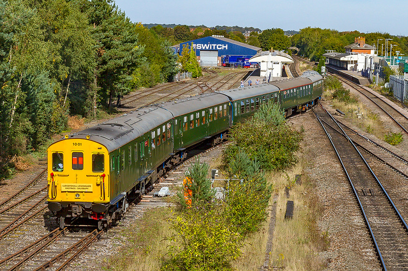 14th Sep 2019:  Hastings unit 1001  comes off the Ludgershall Branch at Andover asit works the 'Ludgershall Legionnaire, from Hastings to Salisbury.  The high viz by the bush is the Network Rail person responsible for operating the points to the main line.