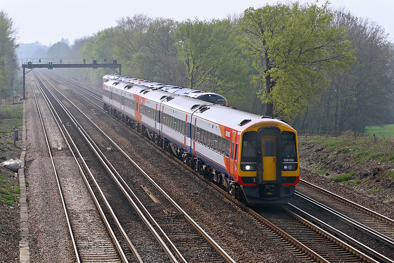 16th Apr 07:  159104 passes 450023 as it races up the short rise between Fleet and Winchfield