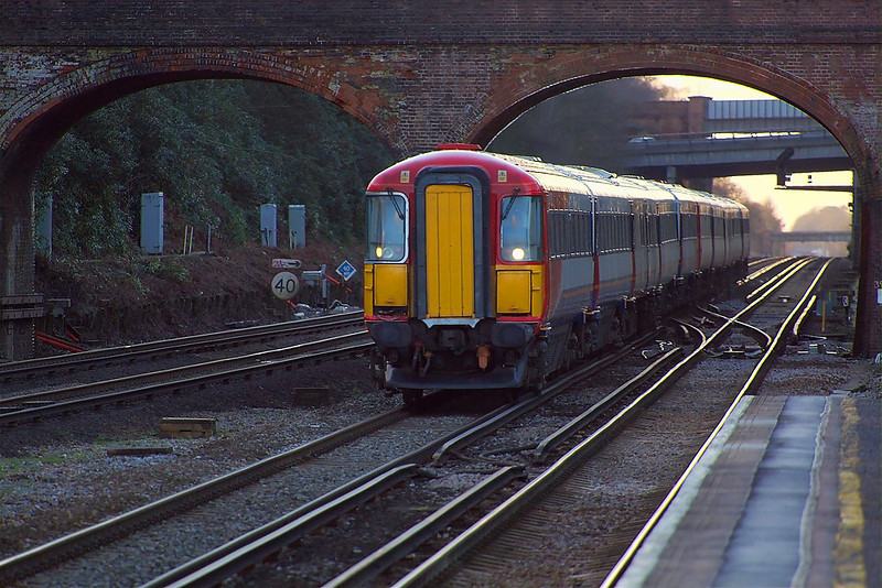 10th Jan 07: The 14.01 Poole to Waterloo formed of 442410&442411 rushes under the bridges at Winchfield. Hook Station, just over 2 miles away, can be seen under the distant Totters Lane bridge