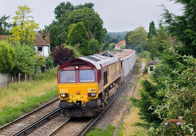 13th Jul:  66 powered today 66162 brings 6V92 under the foot bridge at Egham.  The empty stone boxes are from Woking to Acton Yard