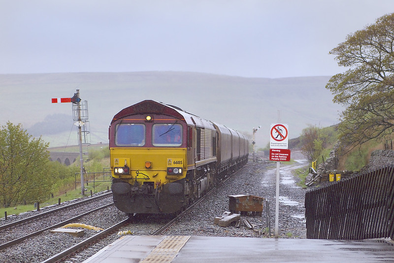 """8th May 07: The """"Gents"""" in Garsdale station provides much needed shelter from the driving rain as 66185 brings  6Z75 New Cumnock to Ratcliffe Power station coal.  The trackbed of the branch to Hawes is visible on the right"""