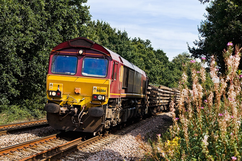 28th Aug 07:  With a load including Sleepers and Autoballasters 66084 roars down grade at the foot crossing north of Mortimer Station on the Departmental from Hinksey to Eastleigh