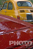 Detail of parked red Ferrari, with yellow  Fiat cinquecento, on cloudy rainy day
