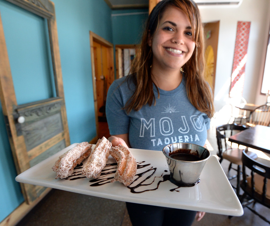 . LYONS, CO: August 29: Kayla Bautista holds cinnamon churros with chocolate dipping sauce. Restaurant Review of  Mojo Taqueria in Lyons, CO on August 29, 2018. (photo by Cliff Grassmick/Staff Photographer).
