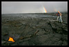 """~ Pele's Pot-O-Gold is Witnessed ~<br /> <br /> Two friends dare to get close enough to an opening into molten earth: a skylight in the roof of a lava tube, exposes a tiny bit of a huge river of lava rushing toward the ocean a mile away. You can see the fuming earth beyond them where the lava tube is still crusted over but releasing sulfur dioxide gasses. The double rainbow was a plus!<br /> <br /> (A close up view of this skylight can be viewed here: <br />  <a href=""""http://leighs-gallery.smugmug.com/Professional/Hawaii-Volcano-Lava-Photos/5485573_99fen/1/518271061_tkbJh/Medium"""">http://leighs-gallery.smugmug.com/Professional/Hawaii-Volcano-Lava-Photos/5485573_99fen/1/518271061_tkbJh/Medium</a>"""