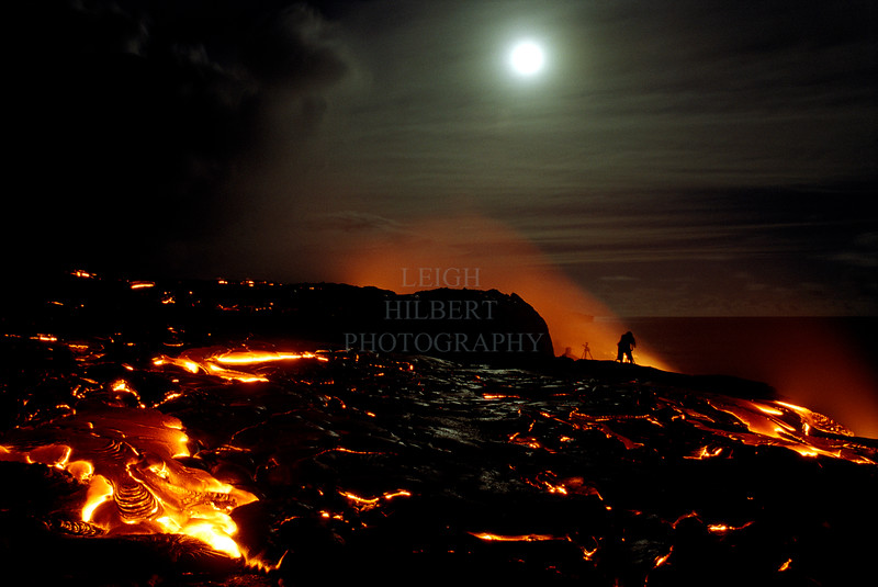 ~ The Photographer ~<br /> <br /> Winter Solstice Full Moon Lava on the southeast shores of the Island of Hawaii.<br /> <br /> (Note the fellow photographer and tri-pod across the molten lava. This guy became trapped there when the lava came down behind him and into the ocean. He was able to find a narrow passage between the flows and head uphill until he found a patch of cooling lava to cross. He burned his boots but survived.