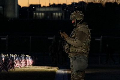 National Guard troop looks at phone on National Mall