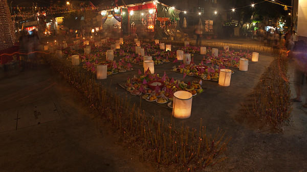 The banquet for the ghosts is laid out in the village square. Villagers offer incense at the perimeter to worship the feasting spirits.