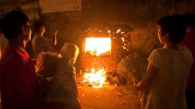 Worshippers wait to burn their offerings to the spirits in a make shift furnace.