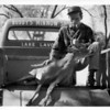"""Buddy Monaghen with deer, note sign painted on the truck, """"Buddy's Minnow Shop"""""""