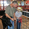 Sean helps Jordan with putting a halter on one of the calves at Harvey County Fair