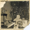 Doug Monaghen, 16 months old, enjoys gifts for Christmas, 1952. This shows the condition of some of the old photos.