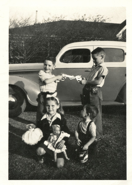 Tom, Dale, Barbara and Boyd Monaghen show off Christmas gifts in the yard at 3212 Milton, Dallas, Texas, late 1940's.
