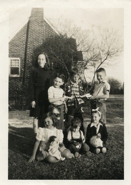Carol Knickerbocker, Tom Monaghen, Winnie Knickerbocker and Dale Monaghen(back row). Unidentified girl, Boyd Monaghen and Barbara Monaghen(front row). Showing off Christmas gifts in front yard at 3212 Milton, Dallas, Texas, late 1940's.