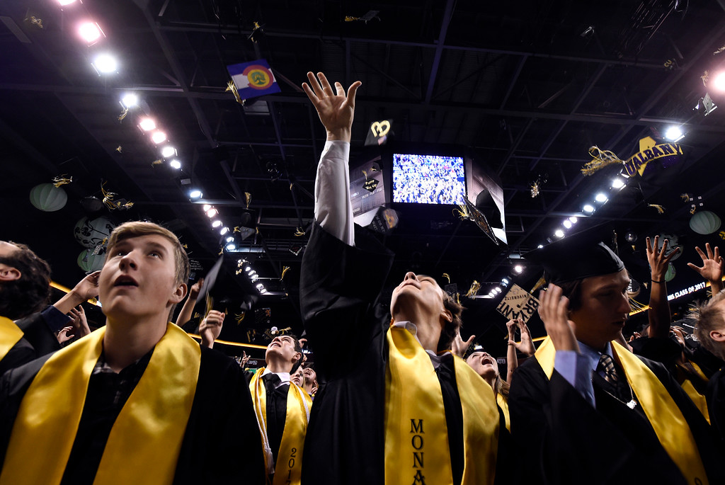 . Monarch High School\'s Jordan Arato, left, and Matteo Bassani, at center, throw their caps into the air during a graduation ceremony on Friday at the 1st Bank Center in Broomfield. For more photos of Monarch High School graduation go to www.dailycamera.com Jeremy Papasso/ Staff Photographer/ May 19, 2017
