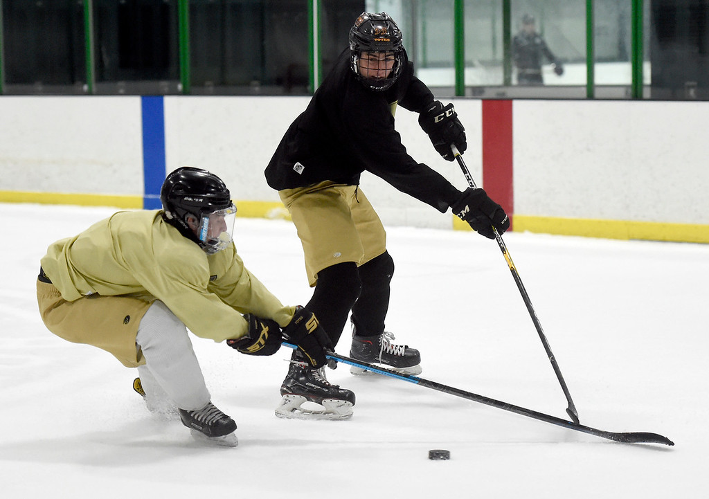 . SUPERIOR, CO - NOVEMBER 28, 2018: Monarch High School hockey player Jake Given, at right, fights for the puck with a teammate during practice on Wednesday at the Sports Stable in Superior. More photos: BoCoPreps.com Jeremy Papasso/ Staff Photographer